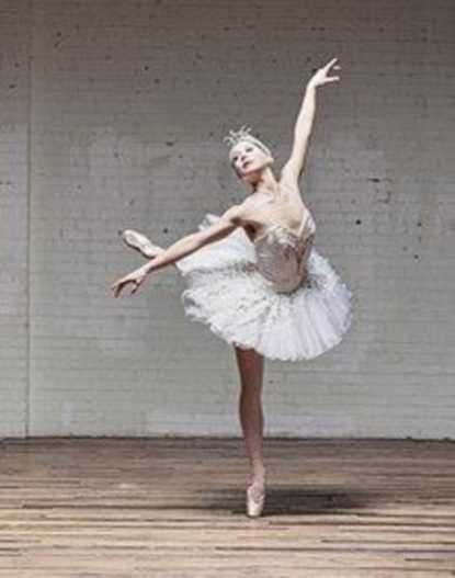 A ballerina stands on her toe and holds out her arms.
