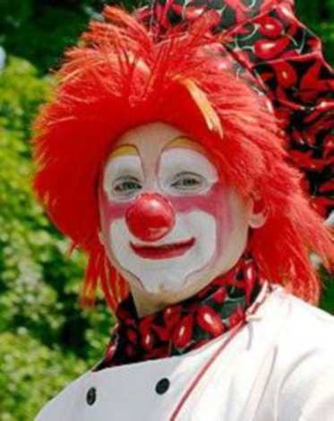 A clown with red hair, white face paint, and a red nose.