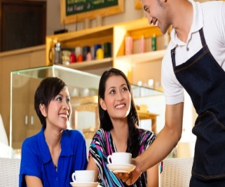 a waiter serving coffee to two women