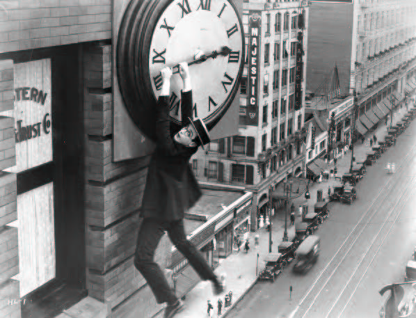 Black and white image of a man hanging from a clock