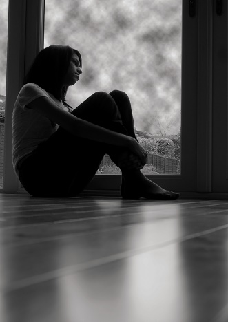 a woman sitting on the floor looking sad