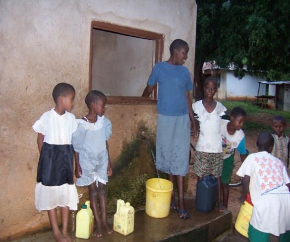 Children collecting water in Bungule Village from a water kiosk that is only open for about an hour every day