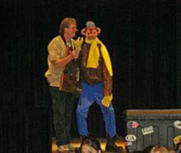 A man on stage holds up a puppet.