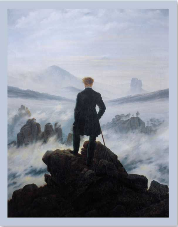 A man standing on a rocky cliff overlooking foggy waters.