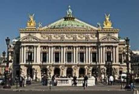 A large building with a green top and two yellow statues on the top sides. It is called the Palais Garnier of the Paris Opera.