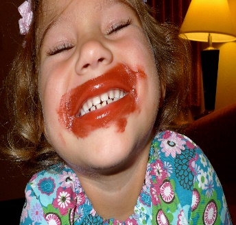 a child with red lipstick all over her face